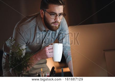 Image of serious designer dressed in shirt and wearing eyeglasses working late at night while drinking tea.