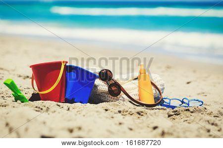 bag, suncream, kids toys on the beach, family vacation