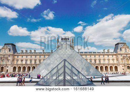 PARIS- JULY 9 : The Louvre Art Museum at sunny summer day under cloudy sky on July 9, 2015 in Paris France