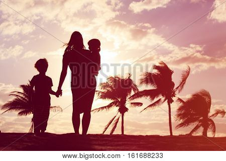 mother and two kids walking at sunset tropical beach