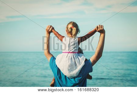 father and little daughter play at beach, family beach vacation