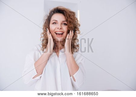 Surprised woman in shirt with open mouth and hands on cheeks looking at camera
