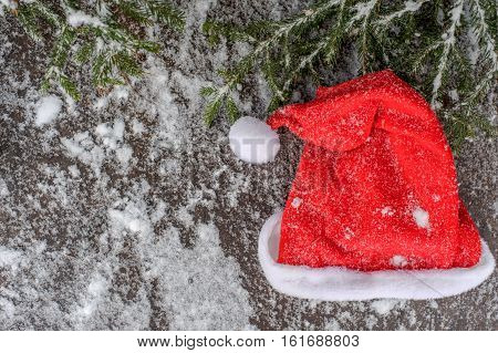 Christmas tree on a wooden board with snow, Christmas green framework with christmas red hat