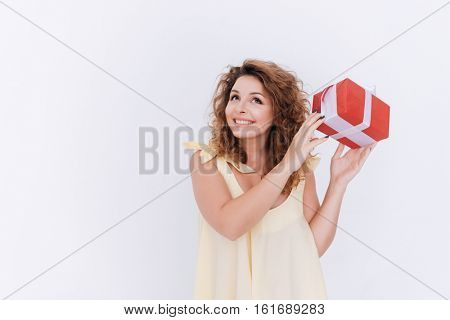 Happy woman in singlet with gift in hands looking up. Isolated gray background