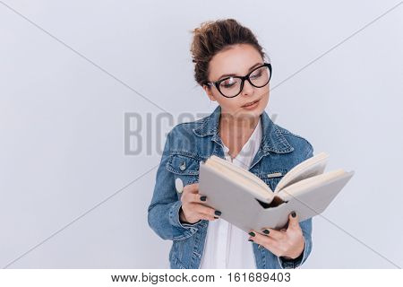Woman in jean jacket reading book in studio. Isolated gray background