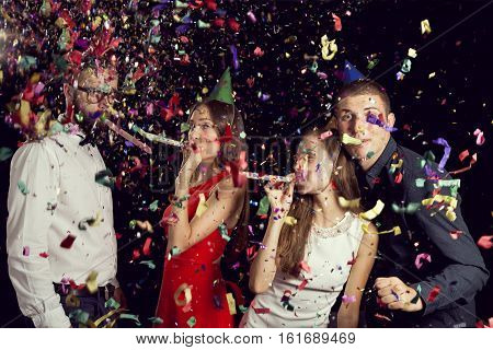 Two beautiful young couples having fun at New Year's party wearing party hats dancing and blowing party whistles.