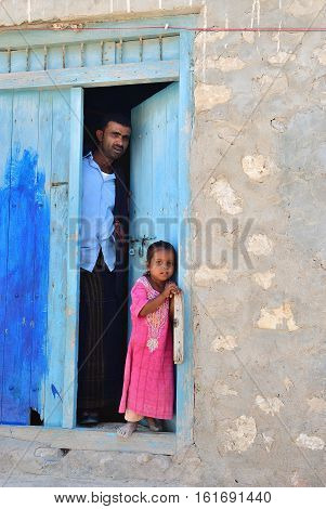 Yemen - March 7 2010: Frightened civilians look out a father and his daughter on the porch of their homes. Among other arabic countries in 2012 Yemen became a site of civil conflicts