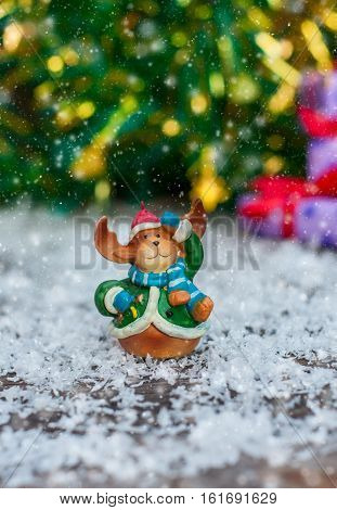 Ceramic Christmas toy elk in festive clothes standing in the snow