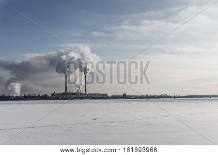 Power station with pipes of which poured smoke on a frozen river. Free copyspace for text. Horizontal image