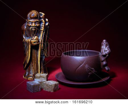 Still life with a statuette of the god of tea a cup and lumps of sugar on red background