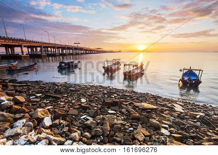 Sunrise rocky shore with fishing boat for background