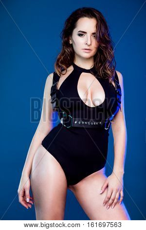 beautiful young sexy woman in black bodysuit and baldric posing in studio