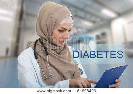 portrait of worried muslim female Medical doctor holding paperclip in hospital. Diabetes sign.