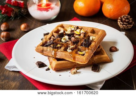 Homemade classic waffles for christmas breakfast on white plate on rustic background with clementine selective focus horizontal