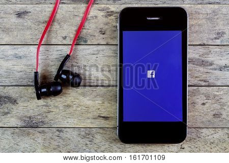 BUNG KAN THAILAND - AUGUST 25 2015: smart phone display facebook app with earphones on a wooden table
