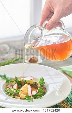 Hand pouring home-made kvass in okroshka served on a white plate