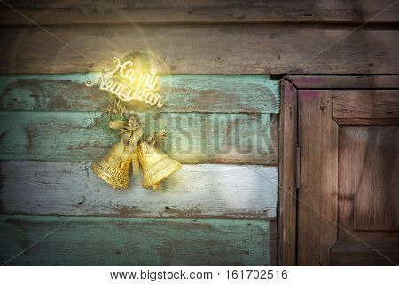 Christmas or New Year rustic hanging over wooden background with bell decorations and fur tree copy space.