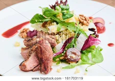 Salad of duck breast, daikon, grapes and couscous served on a white plate