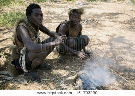 AFRICA, TANZANIA, MAY, 10, 2016 - Two Hazabe bushman of the hadza tribe squatting near the fire and trying to light his pipe. Hadzabe tribe threatened by extinction in Tanzania, Africa