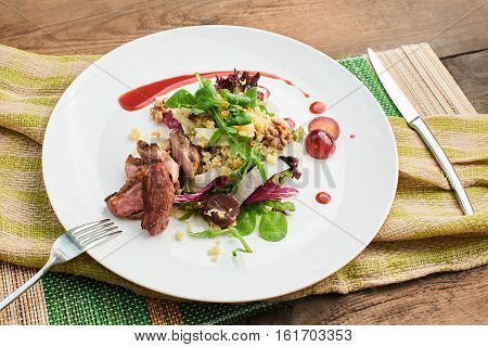 A healthy Breakfast consisting of a salad with duck breast, daikon, grapes and couscous served on a white plate