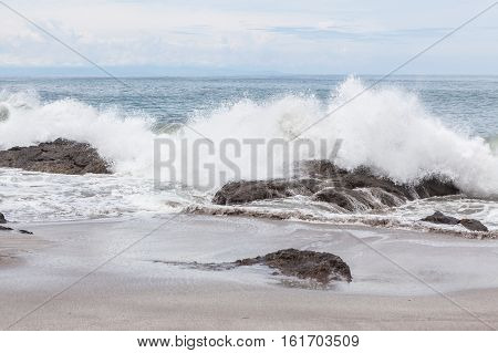 Waves crashing to rocks montezuma beach Costa Rica