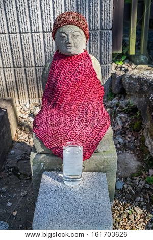 A buddahist statue with a red cloth  sake glass