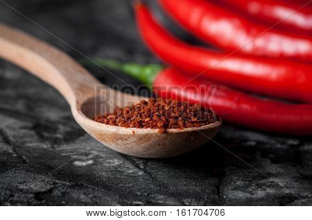 Spoon with seasoning chili and fresh chili on grunge dark background. Food background