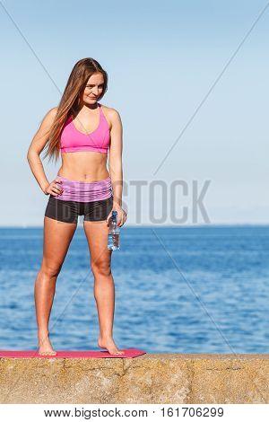 Woman in sportswear takes a break to rehydrate drinking water from plastic bottle resting after sport workout outdoor by seaside