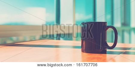 Black Cup Of Coffee In Brightly Lit Room