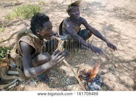 AFRICA, TANZANIA, MAY, 10, 2016 - Two Hazabe bushman of the hadza tribe squatting near the fire and smokes a traditional pipe. Hadzabe tribe threatened by extinction in Tanzania, Africa