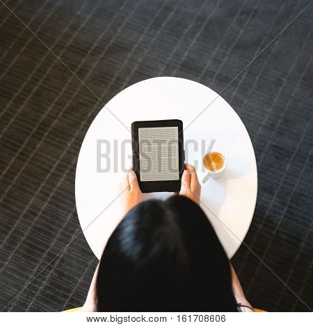 Top Down View Of Woman With E-reader And Coffee