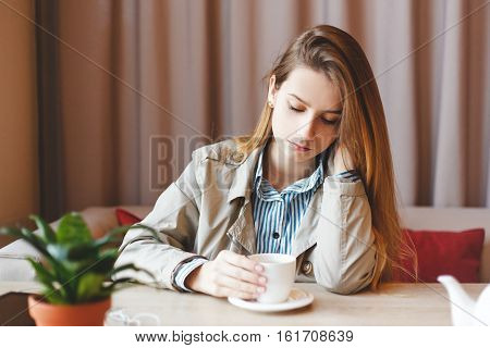 Unemployed woman sits alone heartbroken at coffee shop dwelling in sadness about her lack of career