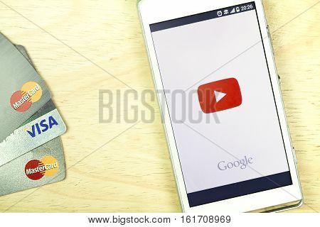 BUNG KAN THAILAND - JANUARY 15 2016: smart phone display youtube app and credit card on office desk