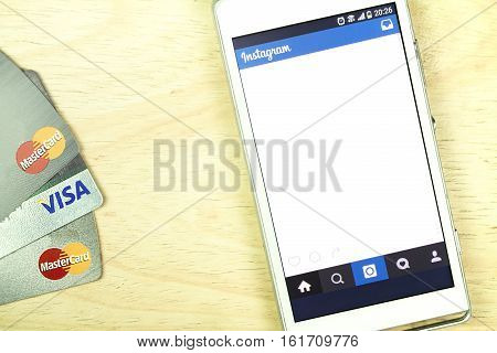BUNG KAN THAILAND - JANUARY 15 2016: smart phone display instagram app and credit card on office desk selective focused