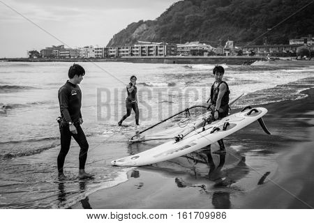 KAMAKURA, JAPAN - NOVEMBER 10, 2016: Surfers on the Pacific beach of Kamakura, Japan. Kamakura is a city in Kanagawa Prefecture, about 50 kilometres south-west of Tokyo.