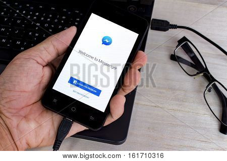BUNG KAN THAILAND - APRIL 5 2016: Smart phone is charging battery and facebook messenger app on screen