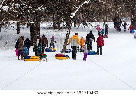 Many Happy families with children playing tobogganing in the winter down. Selective focus. Concepts of active lifestyles, childhood, joy, winter, Christmas, tobogganing. Selective focus.