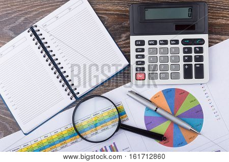 Printout With Charts And Various Office Supplies