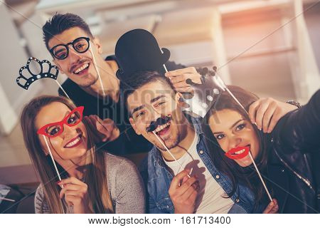 Young friends having a great time in restaurant holding artificial mustache and lips stick making selfie photo