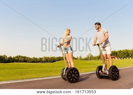 Young Cheerful Man And Woman In Love Driving Segways