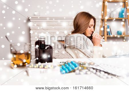 Sick woman with medicament having flu on the background of snowfall
