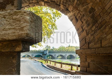 Beziers street alongside Orb River framed by stone bridge pier structure