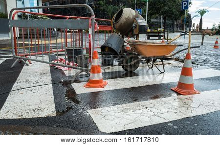 Roadworks in a Town in Madeira with a wheelbarrow some traffic cones and a cement mixer