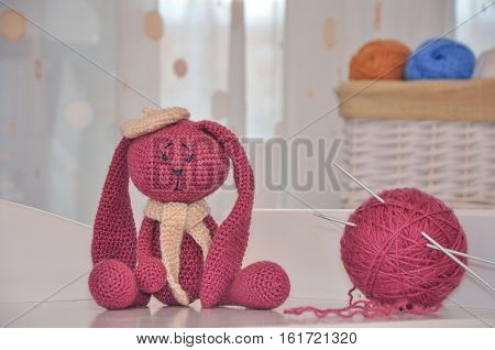 toy rabbit knitted hook. ball of wool and spoke