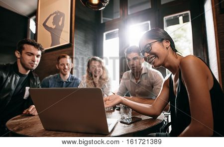 Smiling young woman showing something on laptop to her friends. Group of young men and women at cafe looking at laptop computer and smiling.