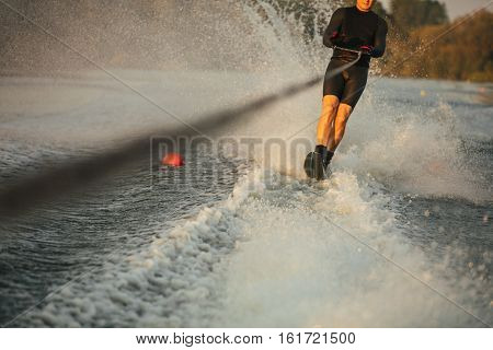 Man riding wakeboard on wave of motorboat in a lake. Male water skiing behind a boat.