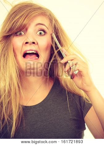 Unpleasant conversation bad relationships concept. Crazy young blonde weirdo woman with messy hair talking on phone