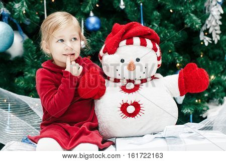 Portrait of happy smiling Caucasian baby girl toddler with blue eyes in red dress sitting by New Year tree near snowman toy emotional lifestyle Christmas holiday concept