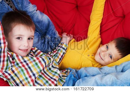 Close-up of two peers on a red soft coach. Two kids relaxing. Wearing casual clothes. Looking at the camera and smiling