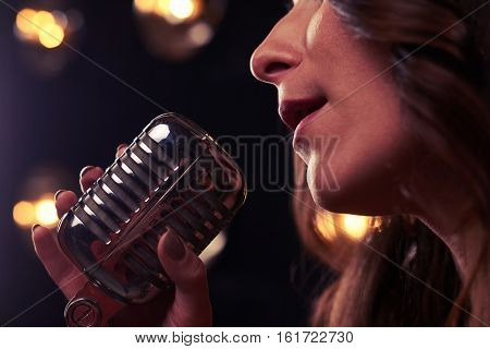 Extreme close-up of female hand holding a vintage microphone. Woman sings in microphone. Microphone isolated over background